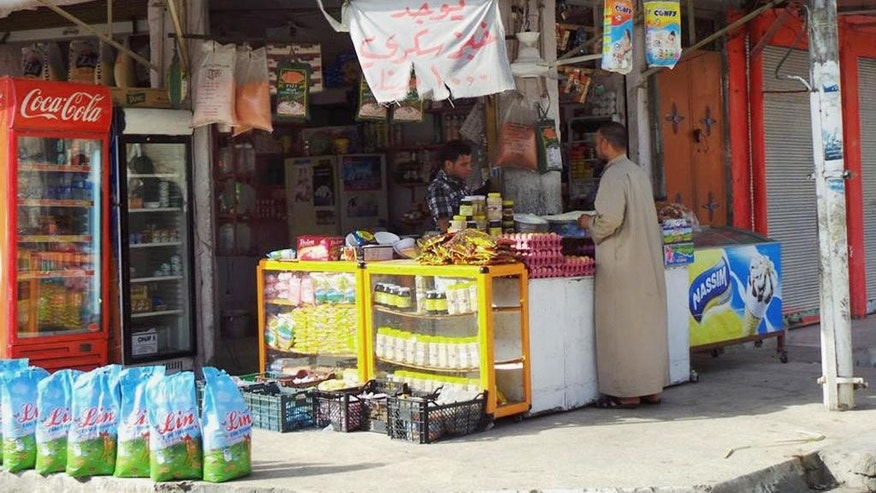June 13, 2014: In this file photo, an Iraqi man shops for food at a market in the northern city of Mosul, Iraq. In the week since it captured Iraq's second-largest city, Mosul, a Muslim extremist group has tried to win over residents and has stopped short of widely enforcing its strict brand of Islamic law, residents say. Churches remain unharmed and street cleaners are back at work.