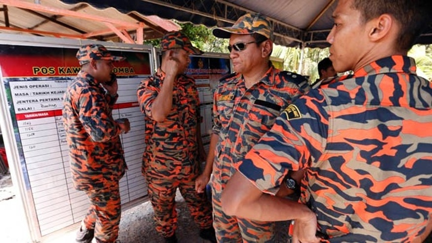 June 18, 2014: Malaysian search and rescue personnel gather to plan for the conduct of a search mission on the outskirt of Banting, Malaysia, Wednesday, June 18, 2014. (AP Photo/Vincent Thian)