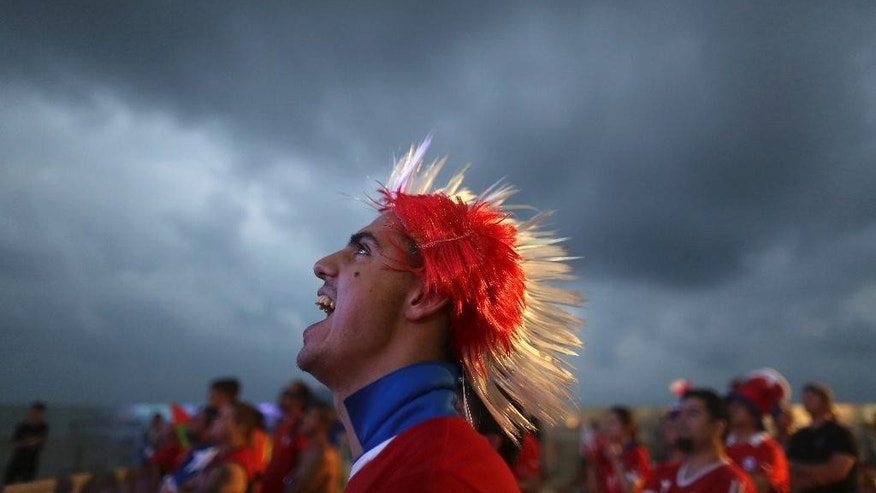 A soccer fan wearing a Mohawk-styled wig in Chile's team colors, cheers as he watches a live broadcast of the group B World Cup match between Chile and Spain, inside the FIFA Fan Fest area on Copacabana beach, in Rio de Janeiro, Brazil, Wednesday, June 18, 2014. Chile defeated Spain, the defending champs, 2-0. (AP Photo/Leo Correa)