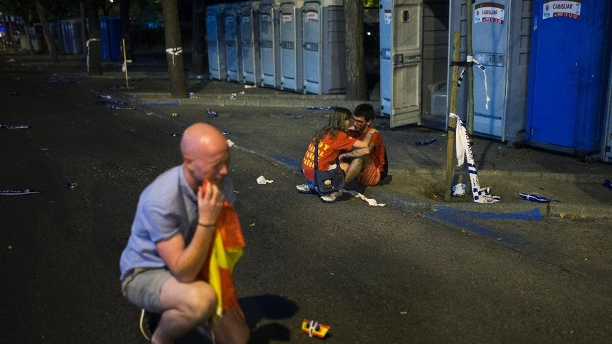 A British fan, left, and his friends, unseen, joke as a Spanish girl consoles her boyfriend, right, at the fan park after the World Cup soccer match between Spain and Chile, in Madrid, Spain, Wednesday, June 18, 2014. Spain lost the match which knocks them out of the World Cup. (AP Photo/Andres Kudacki)