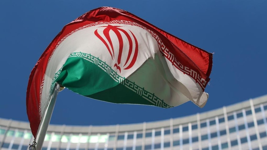 The Iranian flag flies  in front of a UN building where closed-door nuclear talks take place at the International Center in Vienna, Austria, Wednesday, June 18, 2014. (AP Photo/Ronald Zak)