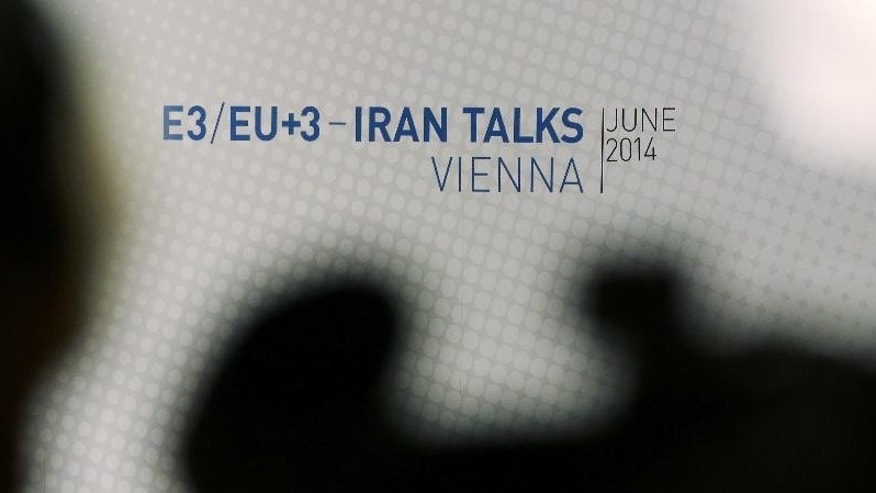 Journalists wait  in front of a poster of the Iran talks  at the International Center in Vienna, where closed-door nuclear talks take place Wednesday, June 18, 2014. (AP Photo/Ronald Zak)