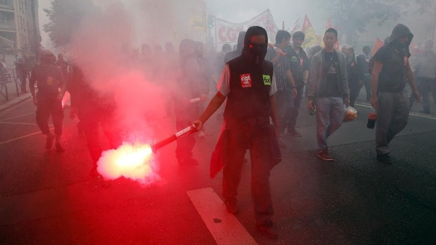 A demonstrator holds a flare during a demontration march of French national railway SNCF in Paris, Thursday, June 19, 2014.  They are striking over plans to streamline and open the state-run network, considered among the world's best, to private competition. A week into a nationwide train strike that has tangled traffic and stranded tourists and has caused some of the worst disruption to the country's rail network in years.(AP Photo/Francois Mori)