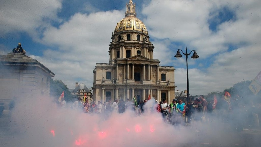 Demonstrators stand front of flares lit by the French national railway SNCF at Invalides War Museum, the burial site for some of France's war heroes, notably Napoleon Bonaparte, during a demonstration march in Paris, Thursday, June 19, 2014.  They are striking over plans to streamline and open the state-run network, considered among the world's best, to private competition. A week into a nationwide train strike that has tangled traffic and stranded tourists and has caused some of the worst disruption to the country's rail network in years.(AP Photo/Francois Mori)