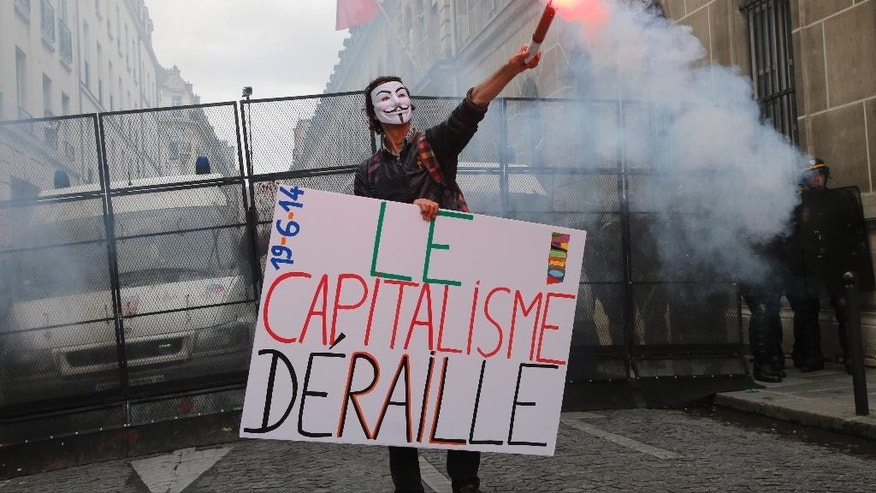 """A demonstrator holds a board reading """"Capitalism Derails"""" in front of a French police roadblock as the French national railway SNCF march in Paris, Thursday, June 19, 2014. SNCF are striking over plans to streamline and open the state-run network, considered among the world's best, to private competition. A week into a nationwide train strike has tangled traffic and stranded tourists and has caused some of the worst disruption to the country's rail network in years. (AP Photo/Francois Mori)"""