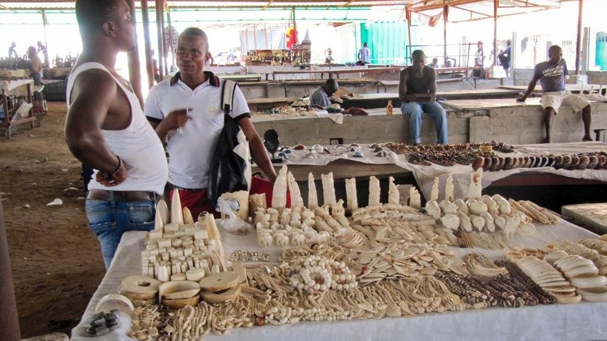In this photo taken Thursday, Feb. 27, 2014 and provided by Esmond Martin, market-sellers stand by souvenirs made of ivory for sale at the Benfica market on the outskirts of Luanda, Angola. The market on the outskirts of Angola's capital sells more than 10,000 pieces of ivory, making it the largest market in southern Africa to openly sell illegal elephant tusks, according to two researchers who traveled to Luanda and surveyed the items of ivory for sale, seeking to raise awareness of the dangers the ivory trade poses to the existence of Africa's elephants. (AP Photo/Esmond Martin)