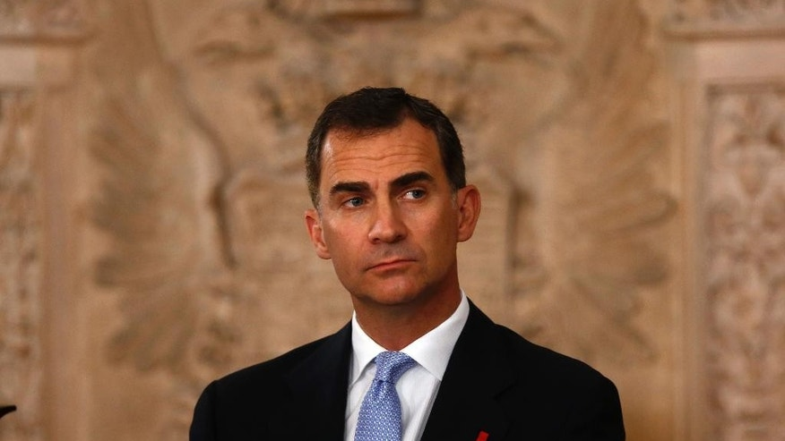 Spanish Crown Prince Felipe stands during a ceremony where Spain's King Juan Carlos signed an abdication law during a ceremony at the Royal Palace in Madrid, Spain, Wednesday June 18, 2014. Spain's Juan Carlos formally ratified the law, signing a legislation setting out the legal framework for the handover so his 46-year-old son can be proclaimed King Felipe VI at a ceremony in Parliament on Thursday. The 76-year-old monarch says he wants to step aside after a four-decade reign so that younger royal blood can rally a country beset by economic problems, including an unemployment rate of 25 percent. (AP Photo/Daniel Ochoa de Olza)