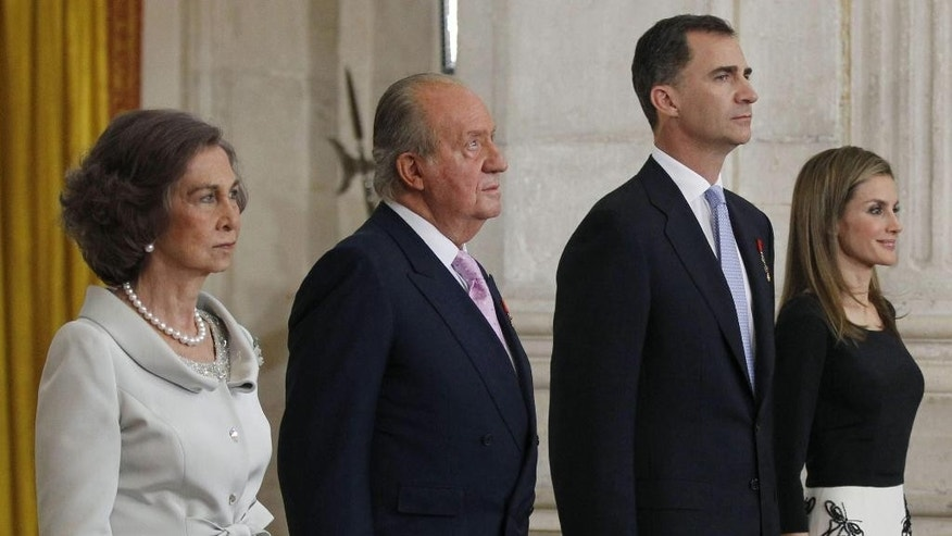 Queen Sofia, left, Spain's King Juan Carlos, 2nd left, Spain's Crown Prince Felipe, 3rd left and Princess Letizia stand during a ceremony where King Juan Carlos  signed an abdication law at the Royal Palace in Madrid, Spain, Wednesday June 18, 2014. Spain's Juan Carlos formally ratified the law, signing a legislation setting out the legal framework for the handover so his 46-year-old son can be proclaimed King Felipe VI at a ceremony in Parliament on Thursday. The 76-year-old monarch says he wants to step aside after a four-decade reign so that younger royal blood can rally a country beset by economic problems, including an unemployment rate of 25 percent. (AP Photo/Alberto Martin, Pool)