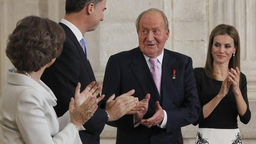 Spain's King Juan Carlos, 3rd left is applauded by Queen Sofia, left, Spain's Crown Prince Felipe, 2nd left and Princess Letizia after he signed an abdication law during a ceremony at the Royal Palace in Madrid, Spain, Wednesday June 18, 2014. Spain's Juan Carlos formally ratified the law, signing a legislation setting out the legal framework for the handover so his 46-year-old son can be proclaimed King Felipe VI at a ceremony in Parliament on Thursday. The 76-year-old monarch says he wants to step aside after a four-decade reign so that younger royal blood can rally a country beset by economic problems, including an unemployment rate of 25 percent. (AP Photo/Alberto Martin, Pool)