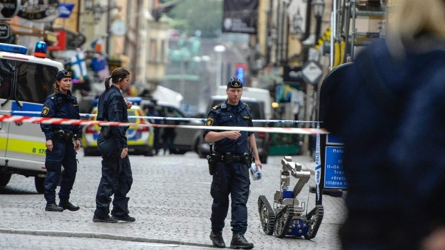 "Police officers and a bomb robot stand in a cordoned off area in central Stockholm, Sweden, Thursday June 19, 2014. Stockholm police say they have closed off and evacuated parts of the city center because of threatening behavior by a man who claims he has a ""dangerous object"" on him. (AP Photo/TT News Agency, Bertil Ericson) SWEDEN OUT"