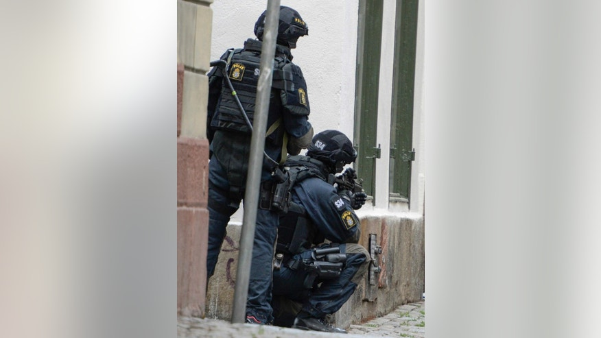 "Armed policemen take position in a closed off area in central Stockholm, Sweden, Thursday June 19, 2014. Stockholm police say they have closed off and evacuated parts of the city center because of threatening behavior by a man who claims he has a ""dangerous object"" on him. (AP Photo/TT News Agency, Bertil Ericson) SWEDEN OUT"