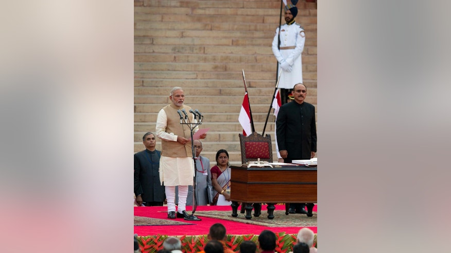 FILE- In this May 26, 2014 file photo, India's Prime Minister Narendra Modi, left, takes the oath of office in Hindi at the presidential palace in New Delhi, India. The top civil servants in in India's labyrinthine bureaucracy these days, are spending their evenings paging through dictionaries, frantically looking up words. The dictionary searches stem from an order by new Prime Minister Modi: All official work must now be done in Hindi, the language spoken by about 45 percent of India's 1.2 billion people. In a country with as many as 22 official languages many question Hindi's dominance. (AP Photo/Manish Swarup, File)