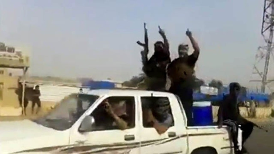 June 17, 2014: In this image taken from video uploaded to a militant social media account, which has been authenticated based on its contents and other AP reporting, Al Qaeda-inspired Islamic State of Iraq and the Levant militants arrive to Iraq's largest oil refinery in Beiji, some 155 miles north of  Baghdad. (AP Photo via militant video)