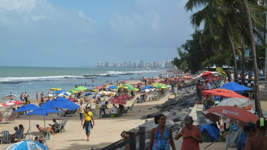 In this June 15, 2014, photo, a throng of beach goers are gathered on Boa Viagem beach in the World Cup city of Recife, Brazil. Boa Viagem, which means safe journey in Portuguese, is notorious in Brazil for shark attacks, and officials have renewed efforts to warn visitors of the danger touring the World Cup. (AP Photo/Lawrence Rincon)