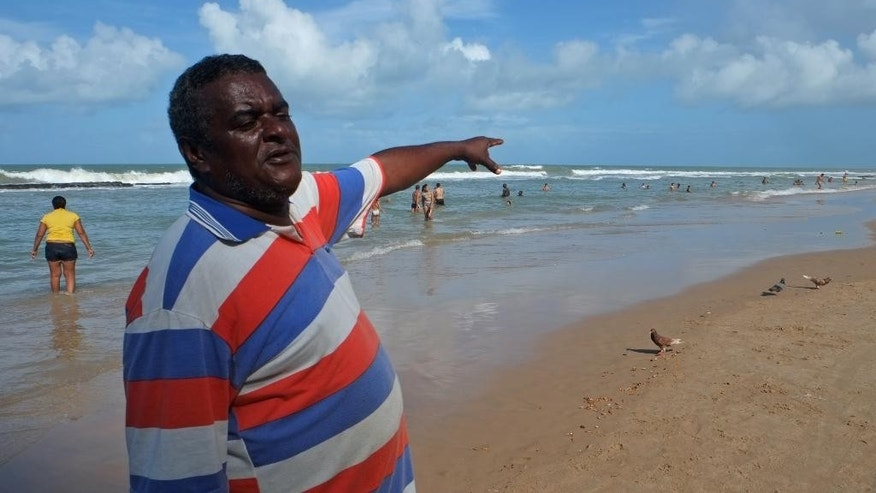 In this  June 15, 2014, photo, David Jose de Lima, who rents chairs and umbrellas at Boa Viagem beach, points to a spot where an 18-year-old Sao Paulo woman was killed in a shark attack in July 2013, in Recife, Brazil. De Lima considers it part of his job to tell everyone new to the beach about the dangers and always issues a warning for swimmers not to cross the reef into open water. (AP Photo/Lawrence Rincon)