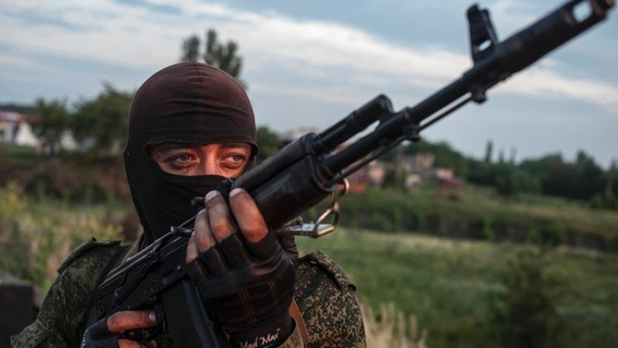 June 18, 2014: In this file photo, a pro-Russian fighter holds a gun during a handover of the bodies of Ukrainian troops killed in a plane shot down near Luhansk, at a checkpoint in the village of Karlivka near Donetsk, eastern Ukraine. (AP)