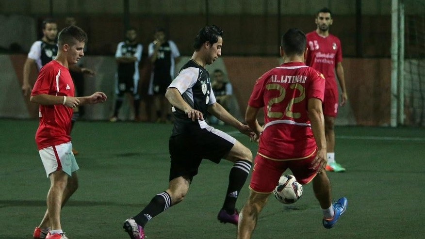 In this photo taken on Tuesday June 10, 2014, Mohammed Meslamani, center, a player of Syrian opposition team, made up of former professional and national youth soccer players who became refugees in Lebanon, fights for the ball against Lebanese players, left and right, during a match against a Lebanese team, at a makeshift pitch in Tripoli, north Lebanon. The squad of refugee players are formally known as the Free Syrian National Team. On rare occasions, when they play against a local club in the northern Lebanese city of Tripoli, they sport their version of the national uniform: black-and-white jerseys adorned with a Syrian revolutionarily flag with three _ instead of two_ stars, pressing against their hearts.  (AP Photo/Hussein Malla)