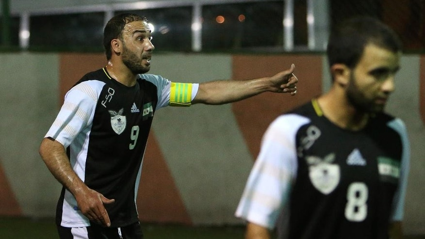 In this phototaken on Tuesday June 10, 2014, Nuhad Saadeldeen, left, the captain of Syrian opposition team, made up of former professional and national youth soccer players who became refugees in Lebanon, reacts after his teammate scored a goal against a Lebanese team, at a makeshift pitch in Tripoli, north Lebanon. The squad of refugee players are formally known as the Free Syrian National Team. On rare occasions, when they play against a local club in the northern Lebanese city of Tripoli, they sport their version of the national uniform: black-and-white jerseys adorned with a Syrian revolutionarily flag with three _ instead of two_ stars, pressing against their hearts.  (AP Photo/Hussein Malla)
