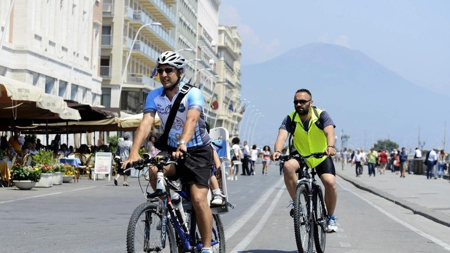"In this Friday, June 13, 2014 photo, Luca Simeone, founder of bike-sharing start up called ""bike tour Napoli,"" left, pedals along a cyclists' path in Naples, Italy. In the background is Mt. Vesuvius. Three years ago Naples' seafront was an urban highway, noisy and smoggy, jammed with car traffic, while smelly trash erupted from garbage bins along streets and alleys. Urban cyclers were regarded as eco-fundamentalists. Three years later, Naples has a new mayor, clean streets, a wide pedestrian beachfront and a 20-kilometer (20-mile) cycling lane overlooking a beautiful bay.  (AP Photo/Salvatore Laporta)"