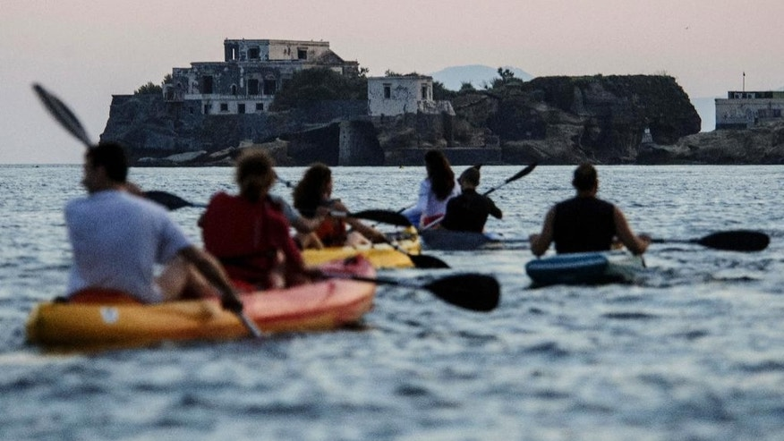 In this Friday, June 13, 2014 photo, tourists enjoy a sunset kayak tour along Posillipo coastline, in Naples, Italy. Three years ago Naples' seafront was an urban highway, noisy and smoggy, jammed with car traffic, while smelly trash erupted from garbage bins along streets and alleys. Urban cyclers were regarded as eco-fundamentalists. Three years later, Naples has a new mayor, clean streets, a wide pedestrian beachfront and a 20-kilometer (20-mile) cycling lane overlooking a beautiful bay.  (AP Photo/Salvatore Laporta)