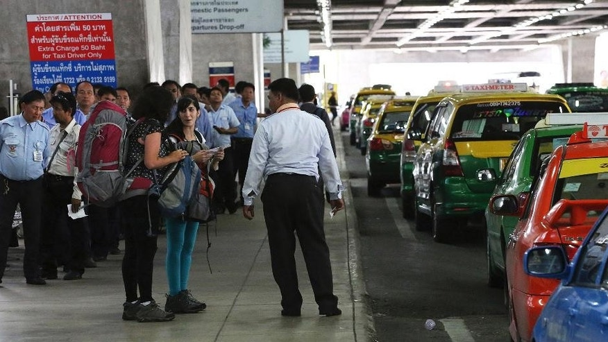 In this photo taken June 19, 2014, tourists, front left, talk to each other in front of a group of taxi drivers at a taxi stand at Suvarnabhumi international airport in Bangkok, Thailand. Since staging a coup on May 22, the military has led a crackdown on crime as part of what army commander Gen. Prayuth Chan-ocha describes as a morality cleanse for Thai society. Before democracy can be restored, he says, corruption and lawlessness have to stop. (AP Photo/Apichart Weerawong)