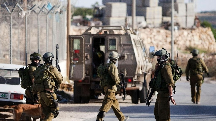 Israeli soldiers search for three missing teens believed to have been abducted in the West Bank city of Hebron, Thursday, June 19, 2014. Since the operation to locate the teens began a week ago, about 280 Palestinians have been arrested, the military said, including 200 members of Hamas. (AP Photo/Majdi Mohammed)