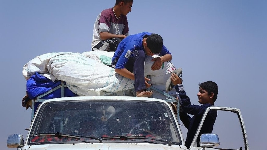 Iraqis who have fled the violence in their hometown of Mosul unload their car at Khazir refugee camp outside of Irbil, 217 miles (350 kilometers) north of Baghdad, Iraq, Monday, June 16, 2014.  Sunni militants captured a strategic city along the highway to Syria on Monday, moving closer to their goal of linking areas under their control on both sides of the border. The al-Qaida breakaway group leading the push in Iraq also is fighting in the civil war next door in Syria where it controls territory abutting the Iraqi border.(AP Photo)