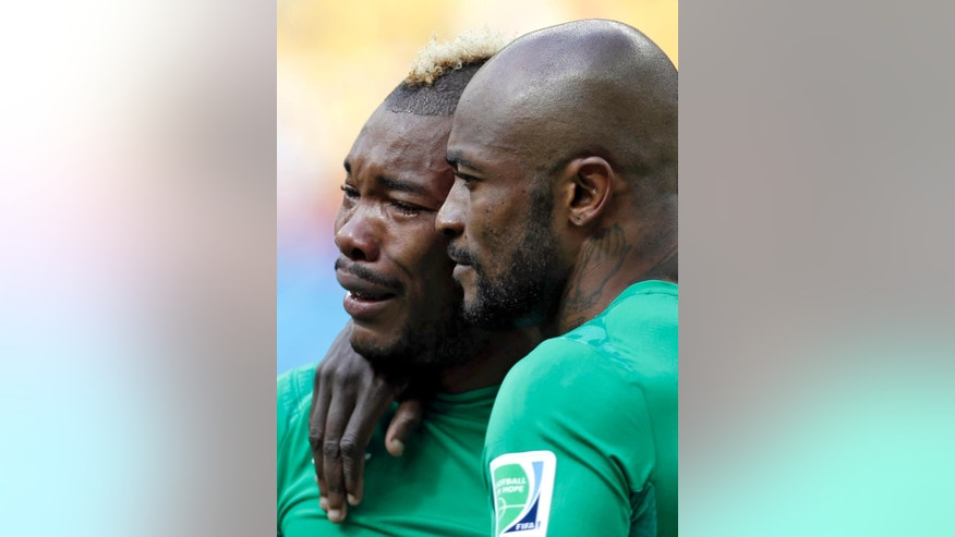 Ivory Coast's Serey Die, left, is comforted by Didier Zakora after he was overcome with emotion as they play the national anthem before  the group C World Cup soccer match between Colombia and Ivory Coast at the Estadio Nacional in Brasilia, Brazil, Thursday, June 19, 2014.  (AP Photo/Marcio Jose Sanchez)