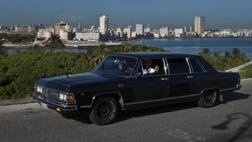 In this June 18, 2014 photo, taxi driver Moises Suarez navigates the Soviet-made limousine that he rents from the government in Havana, Cuba. Today the fleet of limos that were once part of Fidel Castro's fleet have been decommissioned and repurposed as Havana taxi cabs, at the service of tourists who want a little slice of history to go with their ride across town. (AP Photo/Franklin Reyes)