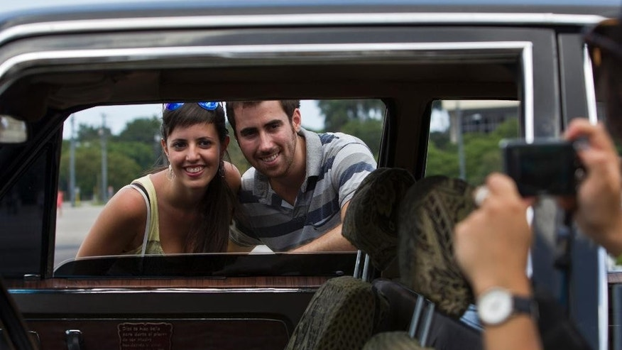 In this June 18, 2014 photo, tourists from Barcelona, Spain take a picture through the window of a Soviet-made limousine taxi cab that was once part of Fidel Castro's fleet in front of Revolution Plaza in Havana, Cuba. The luxury automobiles were produced by Russian manufacturers GAZ and ZIL in the 1960s and '70s. Those sent to Cuba reportedly included a ZIL-111 convertible model that was the first of its kind to roll off the assembly line, a personal gift to Castro from Soviet leader Nikita Khrushchev. (AP Photo/Franklin Reyes)