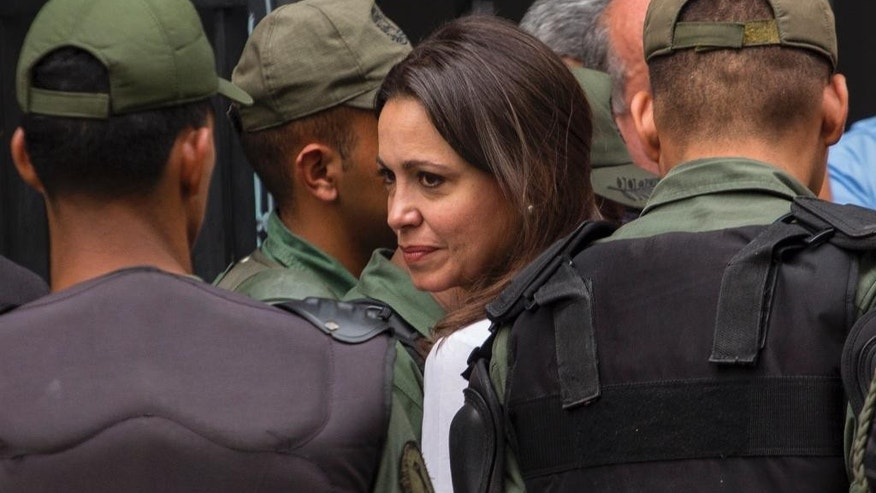 Venezuela's former opposition lawmaker Maria Corina Machado, center, arrives at the Attorney General's office, in Caracas, Venezuela, Monday, June 16, 2014. Machado is expected to testify in an investigation looking into the alleged plot to assassinate President Nicolas Maduro. (AP Photo/Ramon Espinosa)