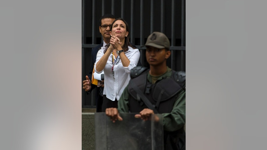 Venezuela's former opposition lawmaker Maria Corina Machado greets supporters as she arrives at the Attorney General's office in Caracas, Venezuela, Monday, June 16, 2014. Machado is expected to testify in an investigation of the alleged plot to assassinate President Nicolas Maduro. (AP Photo/Ramon Espinosa)