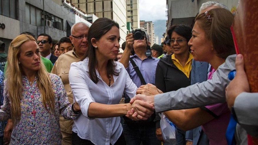 Venezuela's former opposition lawmaker Maria Corina Machado, center, greets supporters as she arrives at the Attorney General's office, accompanied by Lilian Tintori, left, wife of jailed opposition leader Leopoldo Lopez, in Caracas, Venezuela, Monday, June 16, 2014. Machado is expected to testify in an investigation looking into the alleged plot to assassinate President Nicolas Maduro. (AP Photo/Ramon Espinosa)