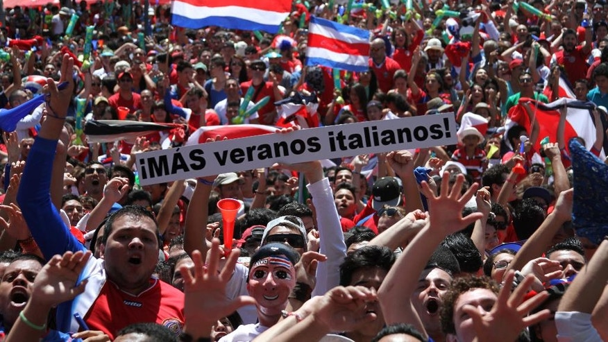"Costa Rica soccer fans celebrate after their team's World Cup victory over Italy in San Jose, Costa Rica, Friday, June 20, 2014. Costa Rica won 1-0. The sign reads in Spanish ""More Italian summers!"" (AP Photo/Enrique Martinez)"
