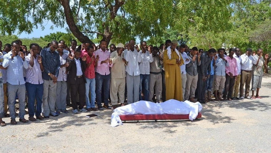 Mourners praying over the body of a Somali journalist, Yusuf Keynan, before burial. The journalist was killed after a bomb planted under his car exploded in Mogadishu, Somali, Saturday, June,  21 , 2014. No group has claimed the responsibility for the assassination of Keynan, the editor of Mustaqbal radio in Mogadishu, who died as he started his car to drive to work early Saturday morning, according to Abdinasir Mohamed Ali, a colleague of the murdered reporter. (AP Photo/Farah Abdi Warsameh)