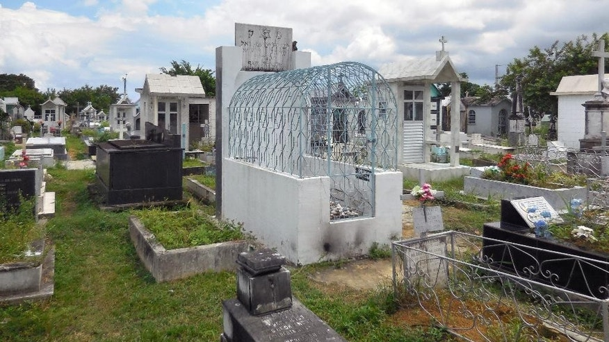 "The tomb of Rabbi Shalom Imanuel Muyal, who died of yellow fever in 1910, lays at Saint John the Baptist Cemetery in Manaus, Friday, June 20, 2014. Muyal is revered by Christians in Manaus as the ""Santo Judeu."" Or, more simply, ""O Rabino."" (AP Photo/Chris Lehourites)"