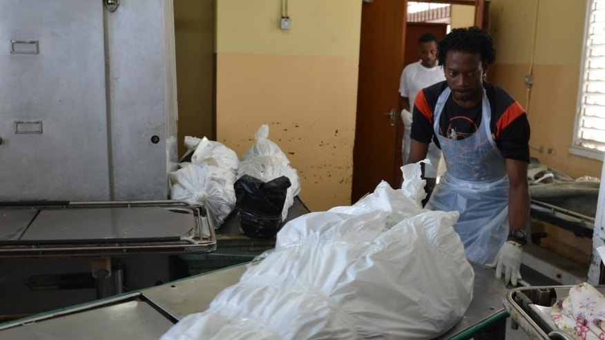 In this Thursday, June 12, 2014 photo, an attendant wheels on a gurney, a body wrapped in plastic, inside the hospital morgue in Spanish Town, Jamaica. The poorly equipped hospital facility is one of the main sites in Jamaica where bodies of people who died violently or under mysterious circumstances are autopsied. Corpses, suspected victims of violent deaths, are wrapped in plastic bags or covered loosely in stained sheets. There is no air conditioning and the room quickly becomes sweltering as the tropical sun beats down on the metal roof. (AP Photo/ David McFadden)