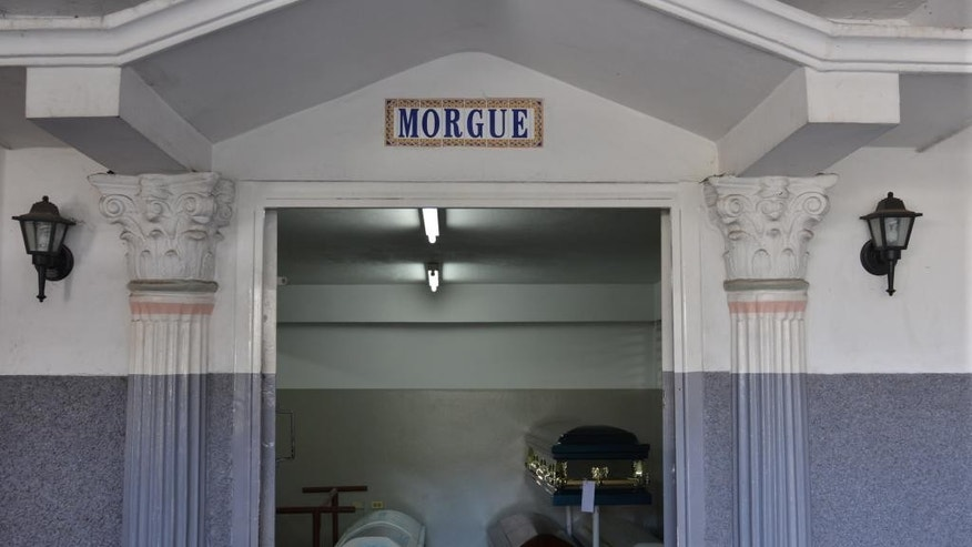 This Tuesday, June 10, 2014 photo shows the morgue entrance to the House of Tranquility private funeral home, in Kingston, Jamaica. The Caribbean island has long had one of the world's highest homicide rates, but it has not had a public morgue for decades even though political leaders have vowed to build one. Instead, funeral homes like the House of Tranquility have a special arrangement with the government to store and collect bodies to be autopsied. (AP Photo/David McFadden)