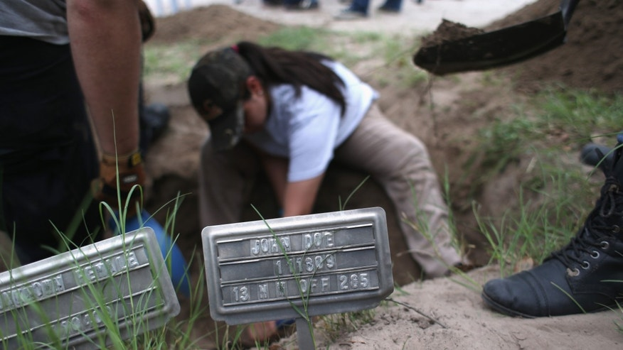 FALFURRIAS, TX - MAY 22:  An anthropology student digs to reach the remains of suspected undocumented immigrants while exhuming bodies from a gravesite on May 22, 2013 in Falfurrias, Brooks County, Texas. In Brooks County alone, at least 129 immigrants perished in 2012, most of dehydration while making the long crossing from Mexico. Teams from Baylor University and the University of Indianapolis are exhuming the bodies of more than 50 immigrants who died, mostly from heat exhaustion, while crossing illegally from Mexico into the United States. The bodies will be examined and cross checked with DNA sent from Mexico and Central American countries, with the goal of reuniting the remains with families.  (Photo by John Moore/Getty Images)