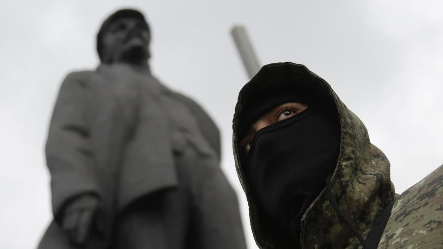 A pro-Russian fighter looks on in Donetsk, eastern Ukraine Saturday, June 21, 2014, with a statue of Soviet Union founder Vladimir Lenin on the left. Ukrainian President Petro Poroshenko ordered his forces to cease fire Friday and halt military operations for a week, the first step in a peace plan he hopes will end the fighting that has killed hundreds. The Kremlin dismissed the plan, saying it sounded like an ultimatum and lacked any firm offer to open talks with insurgents. Separatist leaders have also rejected the ceasefire and said they will not disarm. In Donetsk, a group of armed men gathered in the central square to take a military oath to the self-proclaimed Donetsk People's Republic.  (AP Photo/Dmitry Lovetsky)