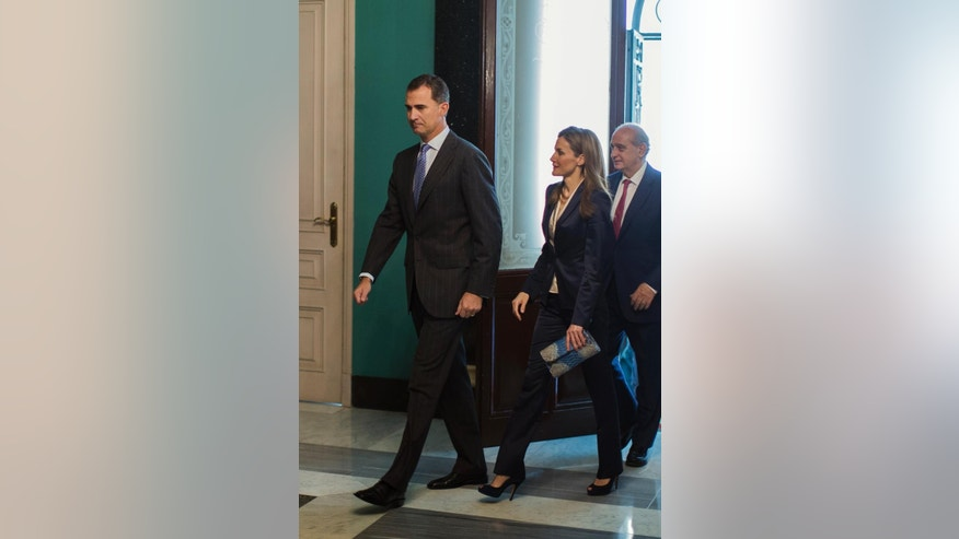 Spain's newly crowned King Felipe VI, left, Queen Letizia, centre, and Spain's Interior Minister Jorge Fernandez Diaz, right, arrive during an event in support of victims of terrorism, in Madrid, Spain, Saturday, June 21, 2014. (AP Photo/Andres Kudacki)