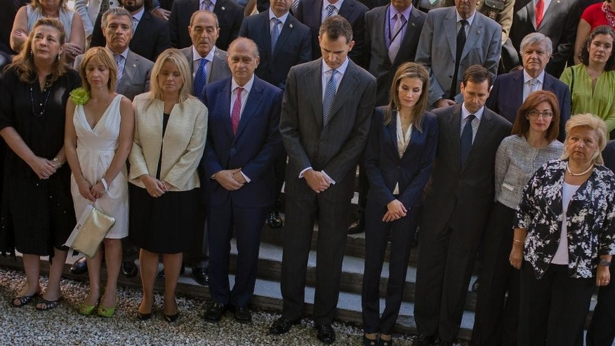 Spain's newly crowned King Felipe VI, center left, Queen Letizia, center right, and Spain's Interior Minister Jorge Fernandez Diaz, fourth left first row, hold a minute of silence in memory of victims of terrorism during an event in Madrid, Spain, Saturday, June 21, 2014. (AP Photo/Andres Kudacki)