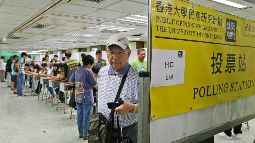 A voter leaves a polling station for an unofficial referendum on democratic reform in Hong Kong Sunday, June 22, 2014. More than 500,000 people have voted in an unofficial referendum on democratic reform organized by the Occupy Central with Love and Peace movement that has alarmed Beijing and sets the stage for a possible showdown with the government, with mass protests aimed at shutting down the Chinese capitalist enclave's financial district.  (AP Photo/Kin Cheung)