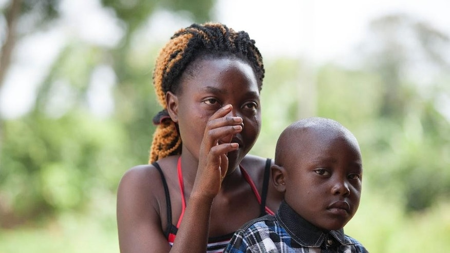 "In this photo of Wednesday, June 18, 2014, Juliet Nabirye wipes tears from her face as she sits with her son,  during an interview with the Associated Press, in Kampala, Uganda. When a child goes missing, the villagers beat drums into a soaring rhythm that sends rescuers scampering through bushes. Others, riding motorcycles, try to block exit routes.  Nabirye, described how one January evening a former boyfriend stole her four-year-old son and told her to ""forget about the child because you will never see him again."" The man, an itinerant with no known home, had a history of criminal behavior and authorities believed the boy was in serious danger. So they drummed alerts and mounted a public campaign to find the child until the man released the boy to strangers who then handed him over to the police. (AP Photo/Rebecca Vassie)"