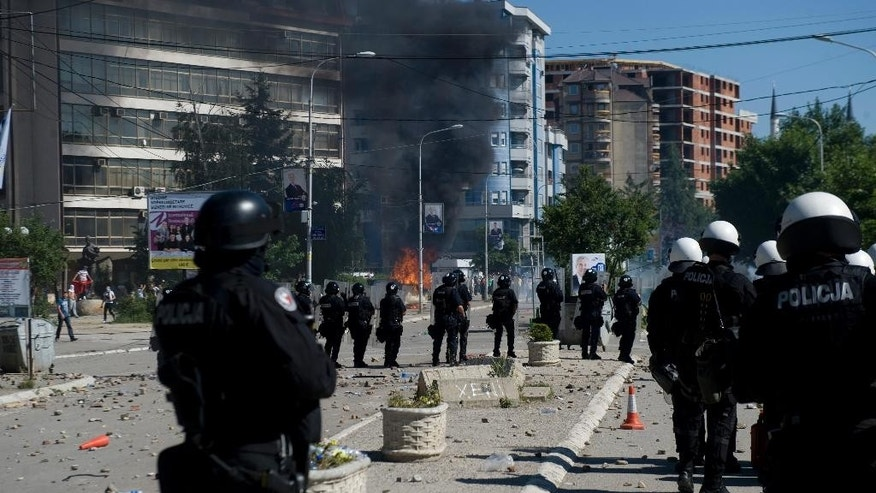 Kosovo police in riot gear deploy to disperse a crowd of hundreds of stone-throwing protestors  who demanded removal of a blockade of flower pots on a bridge linking ethnic Albanians and Serbs in the ethnically divided town of Mitrovica on Sunday, June 22, 2014. Police said at least seven officers were injured as some 5 cars set ablaze as ethnic Albanian protested ethnic Serbs barricading the Serb run north from the ethnic Albanian south. (AP Photo/Visar Kryeziu)