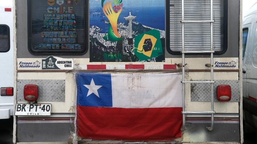 A motorhome decorated with a Chilean flag and World Cup poster showing a photo of Christ the Redeemer sits parked in the Terreirao do Samba area of Rio de Janeiro, Brazil, Saturday, June 21, 2014. Some soccer fans who came for the World Cup in recreational vehicles were relocated from Copacabana beach to this area designed for events during carnival. (AP Photo/Silvia Izquierdo)
