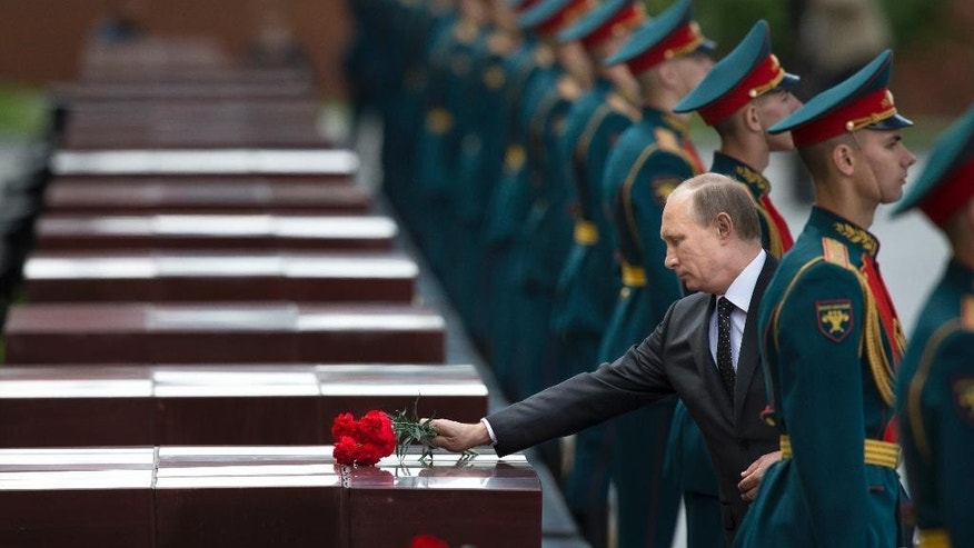 Russian Vladimir Putin, second right, takes part in a wreath laying ceremony at the Tomb of the Unknown Soldier outside Moscow's Kremlin Wall, in Moscow, Russia, Sunday, June 22, 2014,  to mark the 73rd anniversary of the Nazi invasion of the Soviet Union. (AP Photo/Alexander Zemlianichenko)