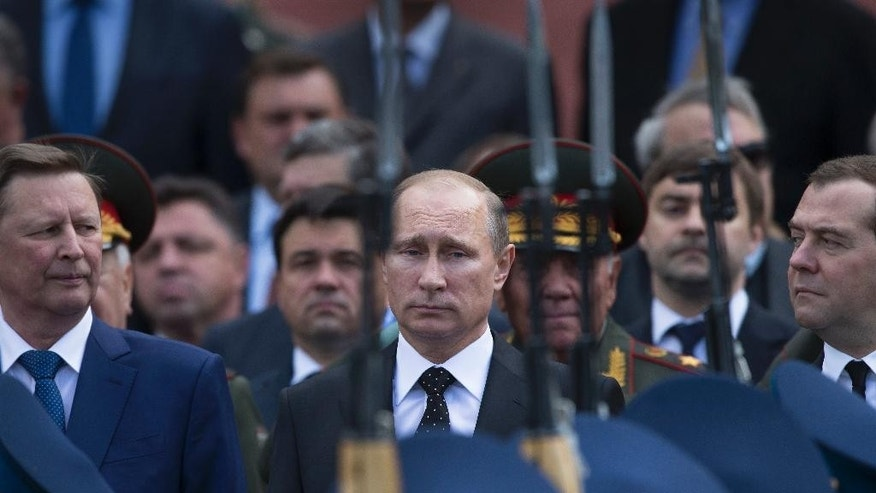 Russian President Vladimir Putin, center, takes part in a wreath laying ceremony at the Tomb of the Unknown Soldier outside Moscow's Kremlin Wall, in Moscow, Russia, Sunday, June 22, 2014, to mark the 73rd anniversary of the Nazi invasion of the Soviet Union. Kremlin's Chief of Staff Sergei Ivanov is on the left, Russian Prime Minister Dmitry Medvedev is on the right. (AP Photo/Alexander Zemlianichenko)