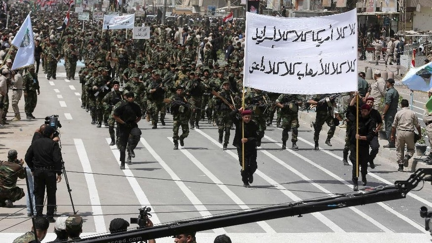 "Volunteers of the newly formed ""Peace Brigades"" participate in a parade in the Shiite stronghold of Sadr City, Baghdad, Iraq, Saturday, June 21, 2014. Thousands of Shiite militiamen have paraded in Baghdad and several other cities in southern Iraq with heavy weaponry, signaling their readiness to take on Sunni militants who control a large chunk of the country's north. The Arabic on the banner reads, ""No for America, No for Israel, No for Terrorism, No for ISIL (the Islamic State of Iraq and the Levant)."" (AP Photo/Karim Kadim)"
