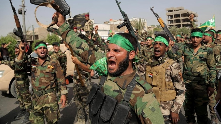 "Volunteers in the newly formed ""Peace Brigades"" raise their weapons and chant slogans against the al-Qaida-inspired Islamic State of Iraq and the Levant during a parade in the Shiite stronghold of Sadr City, Baghdad, Iraq, Saturday, June 21, 2014. The armed group was formed after radical Shiite cleric Muqtatda al-Sadr called to form brigades to protect Shiite holy shrines against possible attacks by Sunni militants. (AP Photo/Khalid Mohammed)"